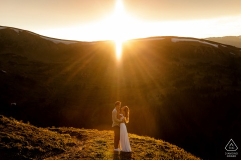 Loveland Pass, CO environmental pre wedding image sessionshowing The sun flares as it dips behind the mountains behind the couple
