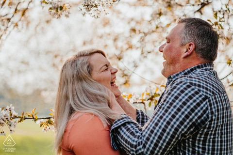 Outdoor Oberhausen, Germany couple engagement photography portrait under blooming trees with fun