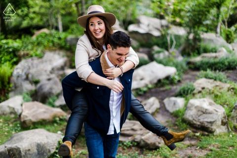 Le Vesinet, France outside environmental couple prewedding photoshootwhile Enjoying some piggyback time at the park