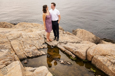 Outdoor Rockport, Massachusetts engagement photography portraitswith the Couple embracing on rocks near ocean with reflection in puddle
