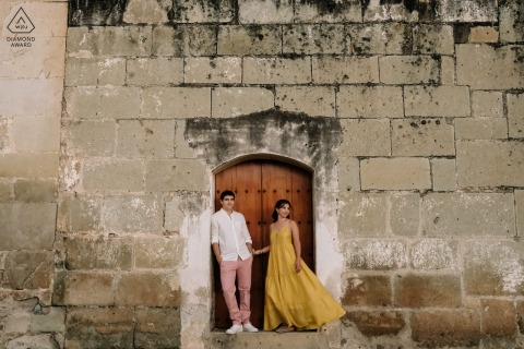 Oaxaca City environmental couple pre wedding image sessionin the doorway of a large stone building