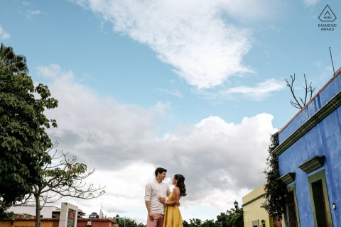 On location Oaxaca City couple engagement portrait shootfrom a low angle under the sky and clouds
