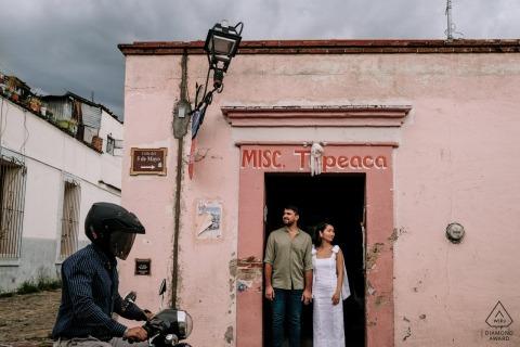 Oaxaca City outside environmental couple prewedding photoshootin the doorway of a small village store