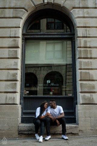 On location Old Montreal, Canada engagement portrait shootwith a couple sitting on a window ledge in front of an old stone building