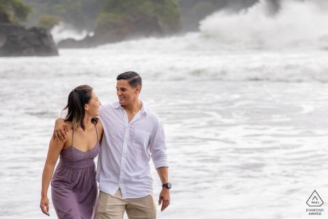 Outdoor Manuel Antonio, Costa Rica engagement photography portraitsas the couple walks on beach
