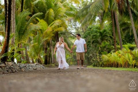 Esterillos Beach, Costa Rica outside environmental couple prewedding photoshootwhile walking hand in hand under the palm trees
