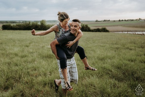 Outdoor Saint Maigrin, France engagement photography portrait of A couple in a field riding piggyback