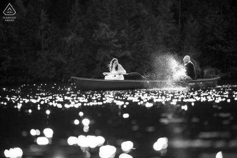 Outdoor Adirondack Park, New York couple portraits de photographie de fiançailles alors qu'il éclabousse son fiancé avec sa pagaie de canoë