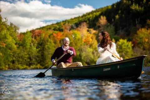 Adirondack Park, New York, couple environnemental, séance d'images avant le mariage alors qu'elle le regarde alors qu'ils pagayent sur le lac en automne