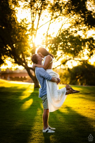 Outdoor Perth engagement photography portraitsshowing The couple dancing together in the sunlight under the trees