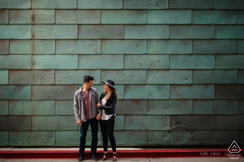 Outdoor Denver engagement photography portrait of a couple in front of a green textured wall