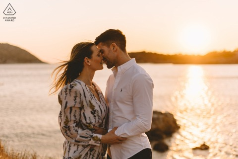 Santorini environmental pre wedding image sessionwith a romantic couple kissing in golden hour