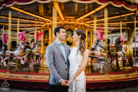 Firenze environmental couple pre wedding image session in front of a blurred carousel at the fair
