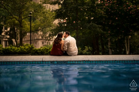 Outdoor Rittenhouse Square, Philadelphia couple engagement photography portrait with a poolside kiss