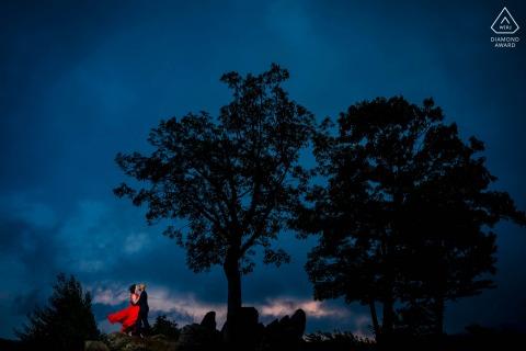 On location Shenandoah National Park engagement portrait shootas the couple embraces as a storm approaches