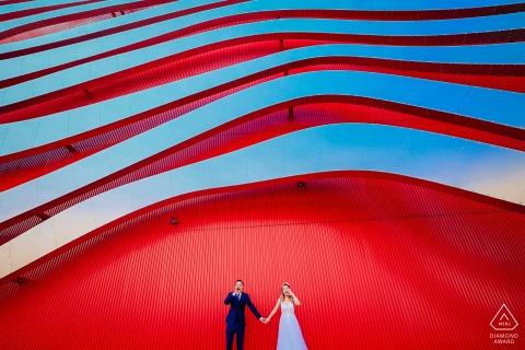 Los Ángeles, CA fuera de la pareja ambiental sesión de fotos previa a la boda que muestra que son felices juntos bajo la pared de arte rojo