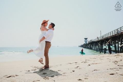 Los Ángeles Beach pareja fotografía de compromiso retratos en las arenas de la costa de CA por un muelle