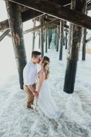 Los Ángeles pareja ambiental sesión de imagen previa a la boda con un beso bajo el muelle de la playa de CA