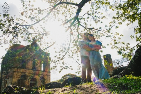 On location São Luis do Quitunde - AL couple engagement portrait shoot with a A warm hug under a large tree