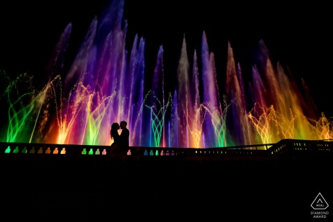 Pennsylvania pre wedding photo at night of couple standing near colorful water fountains
