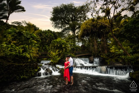 San Jose CR Couple kissing in the middle of a river inside the Tabacon Hot Springs Resort during their engagement session