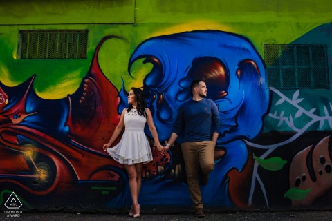 Engaged couple holding hands in front of a big graffiti wall on the streets of Barrio Escalante in San José