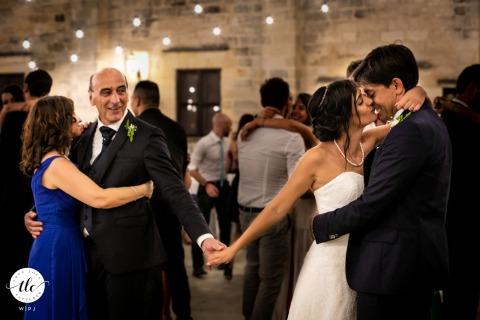 El papá de la novia toma la mano de su hija durante el primer baile con su esposo en Masseria San Lorenzo, Lecce