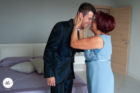 """Casa dello Sposo wedding photographer """"The groom's mother concludes the end of the dressing with a sudden kiss. I try to grasp the stiffness of the body which reveals emotion, in stark contrast to the expression of the face."""""""
