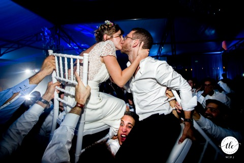 Hauts de France wedding image of the bride and groom being lifted in chairs as they kiss