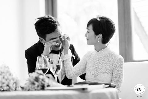 Moment de réception de mariage à Hong Kong photo de la mariée essuyant les larmes du marié alors qu'il pleure