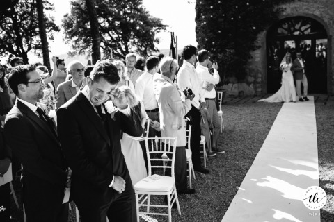 Borgo Tignano wedding moment image from an outdoor ceremony as the Groom is crying when he sees his bride walking down the aisle