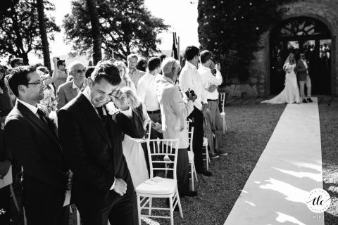 Imagen del momento de la boda de Borgo Tignano de una ceremonia al aire libre mientras el novio llora cuando ve a su novia caminando por el pasillo.