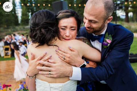 Grey's Crossing, Truckee wedding day moment photo from CA created as The bride and groom embrace a tearful sister of the bride following her emotional speech at an outdoor reception venue