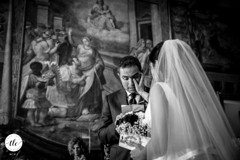 Tivoli Town Hall, Rome wedding moment image showing The bride dries groom's tears whilst he's reading his vow