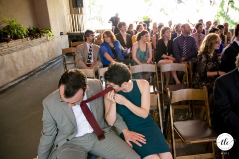 Berkeley City Club wedding ceremony moment photo showing the bride's childhood and lifelong friend who just gave a powerful and emotional speech. She then sits down and uses her husband's necktie to wipe her eyes