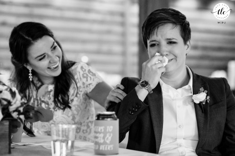 WA image of a wedding moment as the Trinity Tree Farm Issaquah Bride cries while other bride laughs during toast