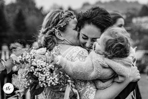 Arette, Pyrénées, France photography of a wedding moment showing A friend and her child embrace the bride with emotion