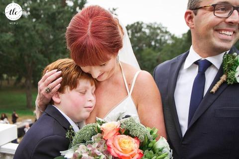 Imagen documental de la boda de Maysville, Georgia de una madre abrazando a su hijo después de la ceremonia