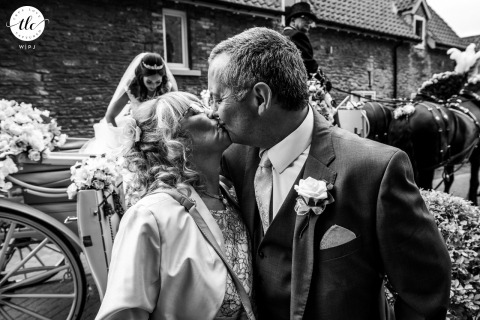 Cave Castle, South Cave, East Yorkshire wedding reportage image of the bride getting out of her wedding carriage, while her mum and dad have a kiss together in the foreground. A lovely and unexpected moment
