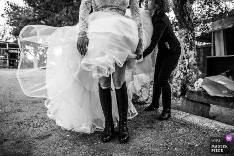 Panna młoda we Włoszech próbuje naprawić swoją sukienkę na buty jeździeckie na zewnątrz na weselu