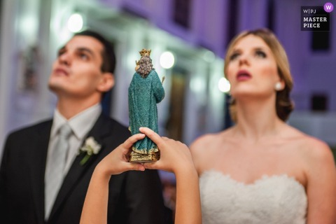 De de bruid en bruidegom van Brazilië kijken omhoog aangezien het kind een cijfer tijdens de ceremonie houdt
