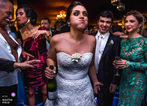 Rio de Janiro wedding photographer captured this image of a bride who took too big a drink from a bottle of champagne