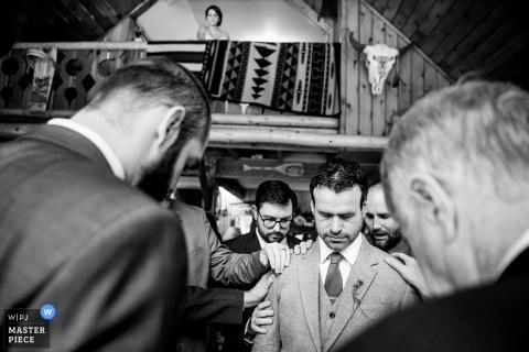 Deze zwart-witfoto van de bruidsjonkers die hun hoofd in gebed buigen terwijl de bruid vanaf een balkon kijkt, werd gevangen door een huwelijksfotograaf van Couer d'Alene
