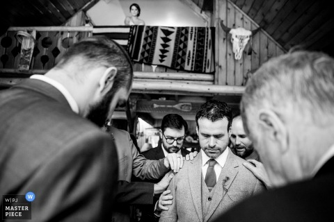 This black and white photo of the groomsmen bowing their head in prayer while the bride watches from a balcony above was captured by a Couer d'Alene wedding photographer