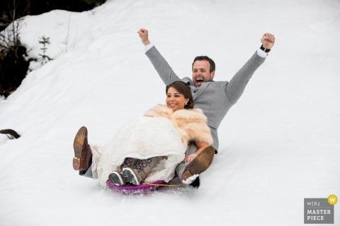 De huwelijksfotograaf van Couer d'Alene heeft deze foto van een bruidegom met zijn handen in de lucht vastgelegd terwijl hij en zijn bruid een besneeuwde heuvel afdrijven