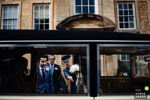 De bruidegom stapt in het voertuig met hulp van de chauffeur in de Barton Hall Hotel & Vines Brasserie