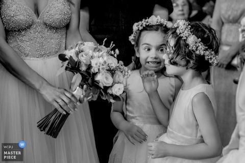 Der Athener Hochzeitsfotograf hat dieses Schwarzweißfoto von zwei Blumenmädchen aufgenommen, die ein Geheimnis teilen, während sie darauf warten, dass sie an der Reihe sind, den Gang entlang zu gehen