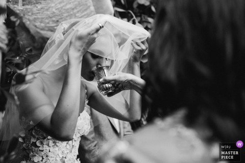 New South Wales wedding photographer captured this bride getting assistance with her drink as she holds up her veil