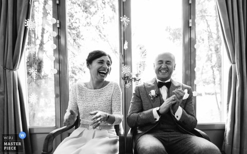 Nouvelle-Aquitaine wedding photographer captured this black and white portrait of a bride and groom laughing in front of a large picture window