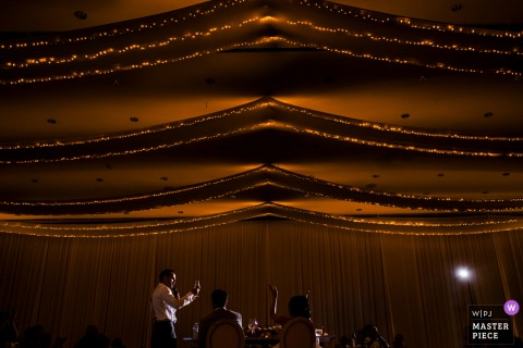 Charleston wedding photographer captures from a distance the best man giving his speech under a curtain of twinkle lights